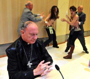 Архиепископ Андре-Жосеф Ленард от Белгия се моли в пълно спокойствие по време на атака, включваща вода и урина, от страна на радикални феминистки и активистки за социална справедливост, съобщава Lentata.com Следвай ме - Вяра